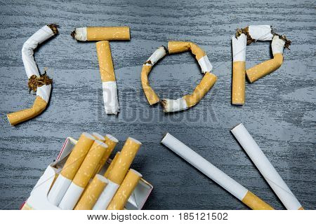 Concept for quitting smoking. Close up of a cigarette pack and Stop smoking sign on the table