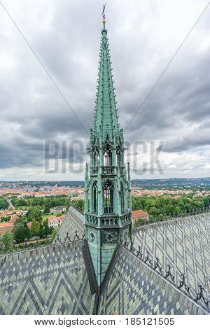 The copper bell tower and roof detail of the St Vitus Cathedral in Prague with the cityscape in the background on a cloudy day.