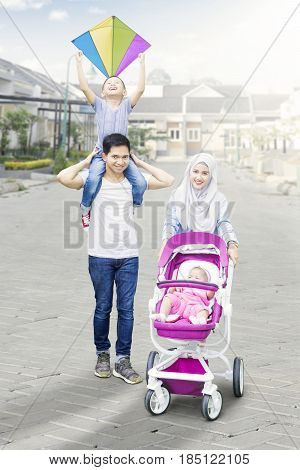 Happy muslim family walking in the new residential street with baby in the pram and their son holding a kite