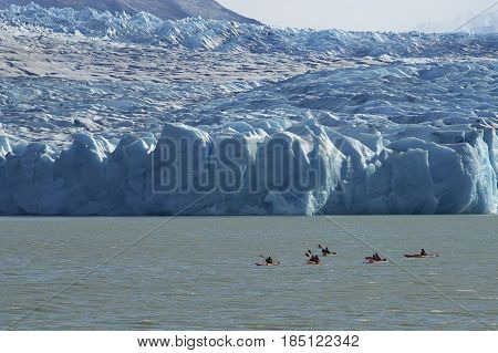 TORRES DEL PAINE NATIONAL PARK, CHILE - APRIL 12, 2017: Group of people kayaking on Lago Grey in Torres del Paine National Park, near the leading edge of Glacier Grey.