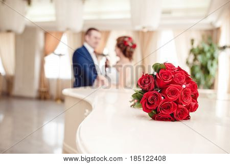 Photo of a bridal bouquet of red roses and pearls on the background of the young marrieds in a beautiful classical hall. Conception is wedding, wedding ceremony, wedding photosession