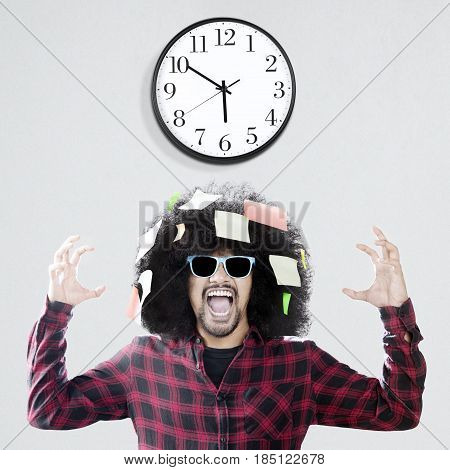 Afro man with curly hair looks frustrated standing under a wall clock while screaming and wearing sun glasses with post it attached on his curly hair