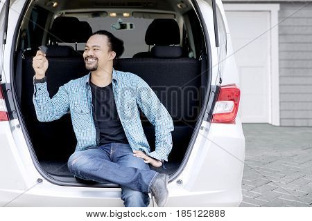 Picture of Afro man looks happy while twisting new car key and sitting behind his car