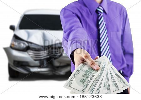 Close up of businessman hand showing dollar money in front of a damaged car after collision