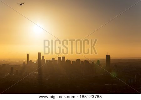 Sunrise over Brisbane with a helicopter, giving a silhouette of the cityscape. Viewed from Mt Coot-tha lookout