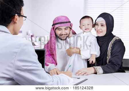Portrait of pediatrician writing a recipe while discussing a medicine with Arabian family in the clinic