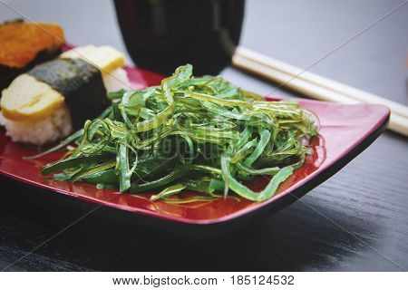 Image of seaweed salad with sushi and chopsticks on the plate over the wooden table