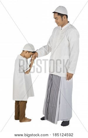 Son kissing a hand from his father as respect gesture isolated on white background