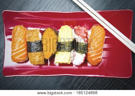 High angle view of sushi pieces served on the red plate with chopsticks over the table