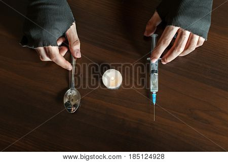 Hands with spoon and heroin syringe closeup, wooden background.