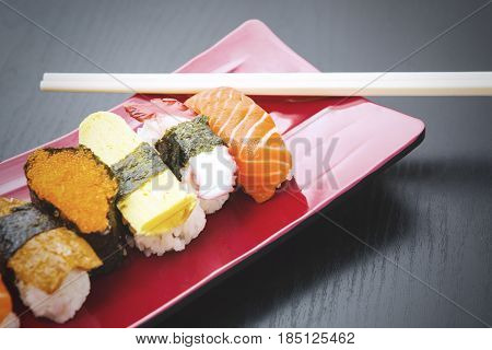 Closeup of variety sushi on the plate with chopsticks over the wooden table