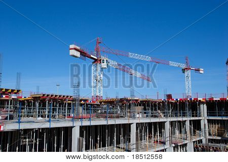 A construction site with a crane and blue sky