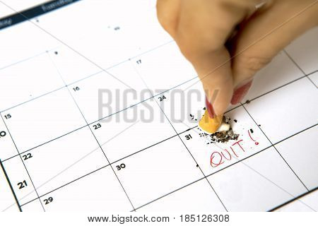 Woman hand destroying a cigarette on calendar with quit word
