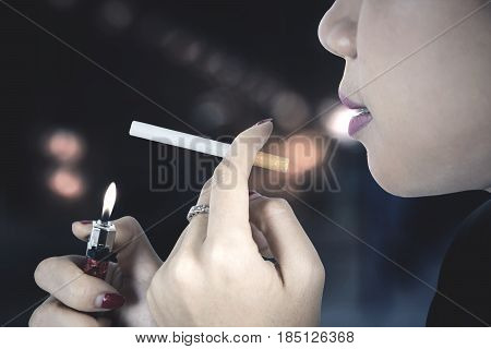 Close up of female smoker burning her cigarette with a lighter shot with blur background