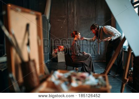 Male artist work with female poseur in art studio