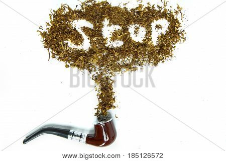 Concept of Quit smoking. Close up of a wooden pipe with stop smoking word made of dried tobacco
