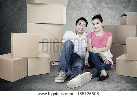 Picture of romantic couple looks tired while sitting with piles of cardboard and looking at the camera