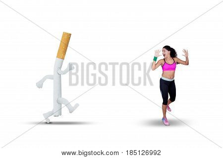 Picture of young Indian woman chased with a cigarette while running in the studio