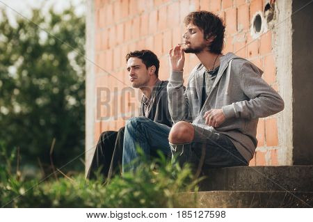 Depressed And Sad Young Man Smoking Cannabis Joint With Friend
