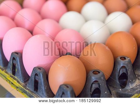 Brown eggs White eggs (Salted eggs) and Pink eggs (Preserved eggs or Century eggs) in a black tray.