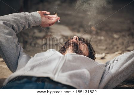 Closeup Of Man Lying On The Ground And Smoke Joint