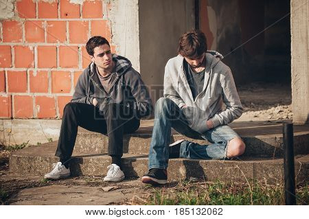 Two depressed and sad young buddies friends thinking together about their problems