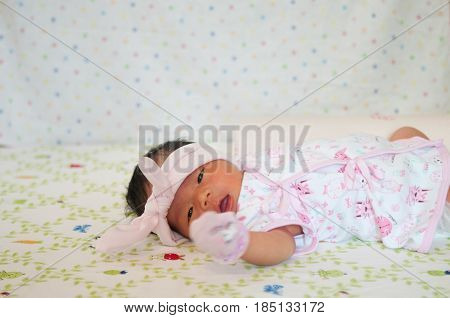 Focus at Baby girl while snoozing and playing on the bed.