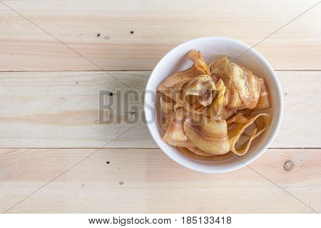 sweet banana crisps on a bowl with wood background