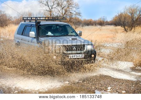 KHABAROVSK RUSSIA - MARCH 25 2017: Mitsubishi Pajero Sport on dirt road in early spring making splashes from a puddle