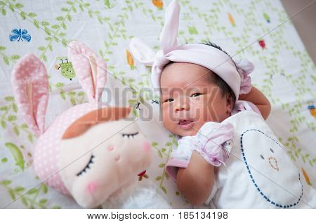 Focus at Baby girl with cute headband while snoozing and playing with cute doll on the bed.
