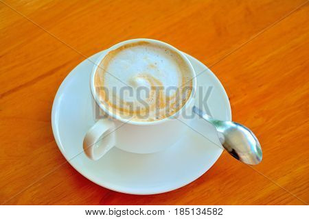 Coffee cup top view on wooden table background.