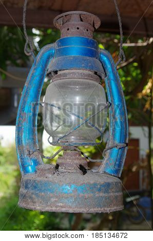 Old blue rusty hurricane lantern hanging under a house.