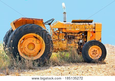 A rusty old farm tractor sits alone in the field on a farm in Thailand. Vintage tractor.