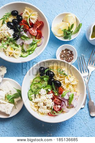 Mediterranean pasta salad. Pasta farfalle tomatoes cucumbers olives feta cheese and arugula salad. On a blue background top view. Flat lay