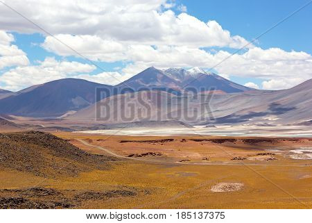 Volcanic mountains landscape of Atacama Desert Chile. Colorful salt flats and mountains on horizon under white clouds.