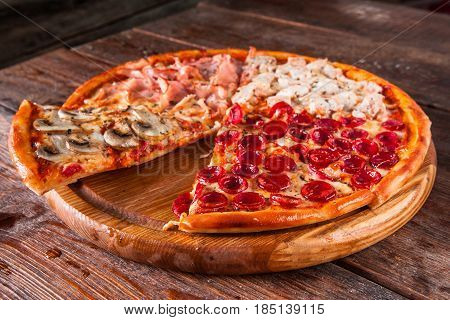 Traditional italian cuisine. Fresh pizza with mushrooms, ham, chicken and sausages with cut slice served on wooden table, top view. Menu photo.