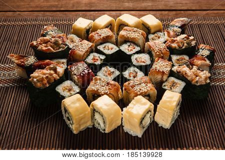 Delicious assortment of sushi, food art. Set of tasty rolls served on straw mat, close up view. Japanese restaurant menu photo, seafood, national cuisine.