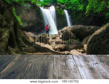 vintage wood terrace with view of young man standing interesting in front of waterfall and take photo by smartphone beautiful waterfall in thailand soft focus and blur due to long exposure.