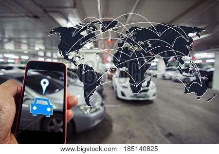 hand holding smart phone with car symbol and world map global connection in intelligent car park concept on blurred parking car indoor background color tone effect.