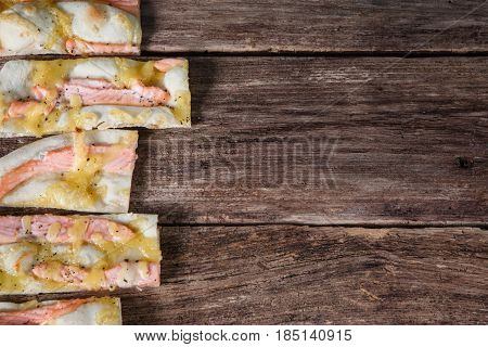 Italian national food background. Slices of appetizing pizza on wooden rustic table with free space for text, flat lay.