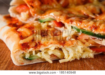 Closeup of fresh baked appetizing slices pizza calzone. Italian traditional food, restaurant menu photo.