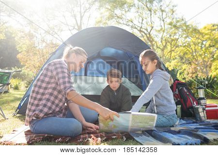 Family reading the map outside the tent on a sunny day