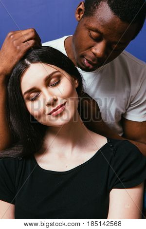 Black man caress white woman hair, closeup. Interracial relationship, international couple in love, tenderness, soft touch, happiness concept.