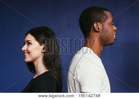 Happy smiling young interracial couple listen music in earphones. Togetherness, happiness, international relationship, fun, bounty concept.