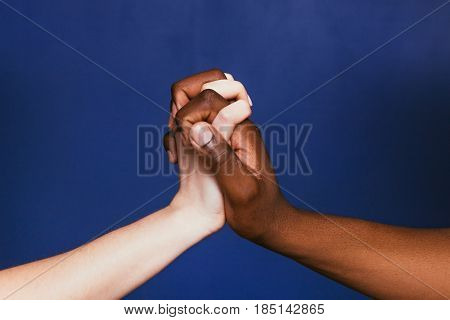 White and black hands of unrecognizable people clasped together on violet background, close up. International relationship, connection, togetherness, contrast, unity concept.