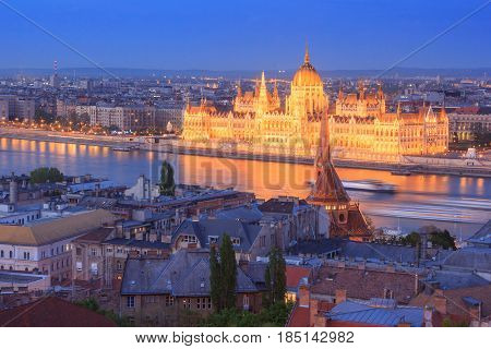 Night view of the famous Hungarian Parliament across the river Danube in Budapest, as seen through the Buda Castle Fishermen's Bastion.