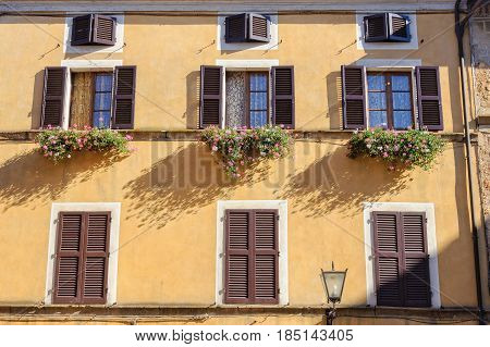 Butter facade with windows, shutters, flower pots and street light - Pienza, Tuscany, Italy