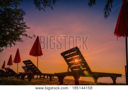 Beach bed and red umbrella on tropical beach at sunset with sun flare.
