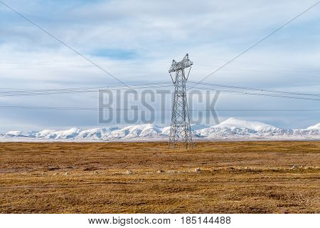 power transmission towers on tibet plateau with snow mountains background