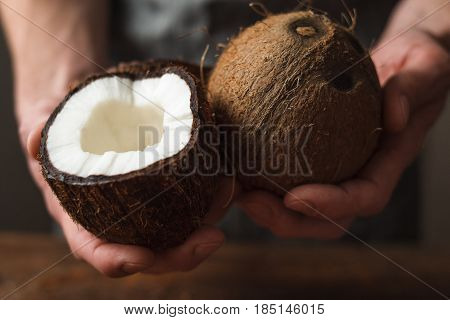 Hands holding fresh coconuts, close up. Culinary masterpiece, cosmetic recipe, organic food ingredient, tropical fruit concept